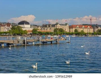Zurich, Switzerland - May 11, 2018: Lake Zurich, buildings of the city, people on a pier. Lake Zurich is a lake in Switzerland, extending southeast of the city of Zurich.