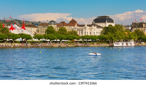 Zurich, Switzerland - May 11, 2018: people on the embankment of Lake Zurich in the city of Zurich, venue of the Circus Knie and the Zurich Opera House building in the background.