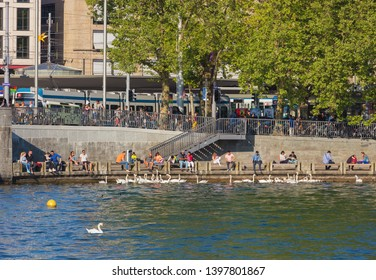 Zurich, Switzerland - May 11, 2018: people on the embankment of Lake Zurich at the Bellevue square in the city of Zurich, swans on the lake. Lake Zurich is a lake in Switzerland.