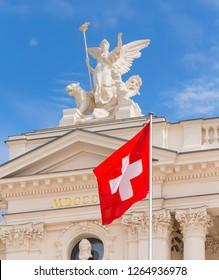 Zurich, Switzerland - May 25, 2016: upper part of the Zurich Opera House building, flag of Switzerland in front of it. Zurich Opera House has been the home of the Zurich Opera since 1891.