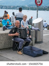 ZURICH, SWITZERLAND - MAY 26, 2018: Elder man plays a traditional accordion on the lake side of Lake Zurich