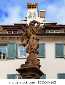 Zurich, Switzerland / November 2019: Woman statue with helmet in fresh water public fountain also featuring street art of two bunnies dancing in the background
