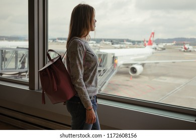 Zurich, Switzerland - November 8, 2017: The girl is standing at the airport in Zurich and looks at the planes on November 8, 2017 in Zurich, Switzerland