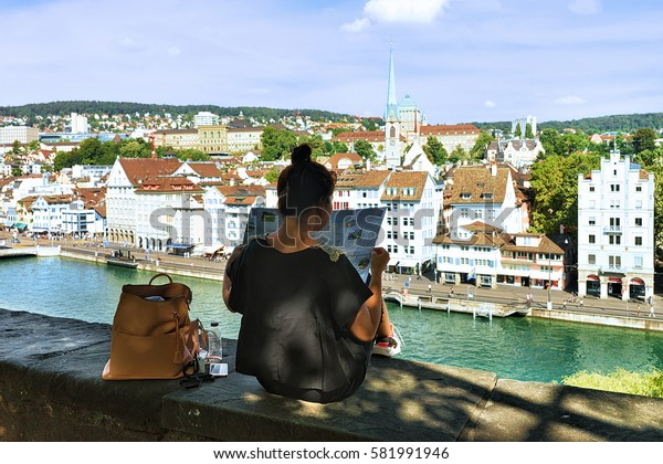 Zurich, Switzerland - September 2, 2016: Girl sitting on Lindenhof hill and looking into a city map in Zurich, Switzerland. Limmatquai and Predigerkirche on the background.
