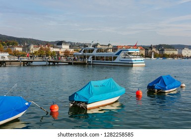 Zurich, Switzerland - September 29, 2017: boats on Lake Zurich at dusk, people on a pier, buildings of the city in the background. Lake Zurich is a lake extending southeast of the city  of Zurich.