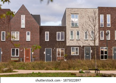 Zutphen, The Netherlands - December 4, 2020: Graphic modern stark playful straight contemporary residential housing in Dutch family neighbourhood on an overcast day with recently laid out park