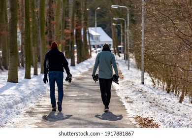 Zutphen, The Netherlands - February 14, 2021: Concept of end of ice skating season with two men seen from behind walking with their skates in hands down a snow free lane backlit by warm afternoon sun