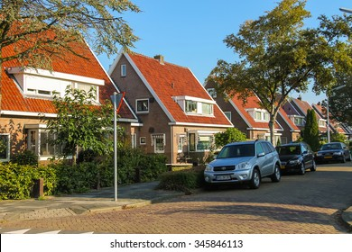 Zwanenburg, the Netherlands - Oct 03, 2015: Picturesque residential houses and parked autos in small town Zwanenburg in the Dutch province of North Holland