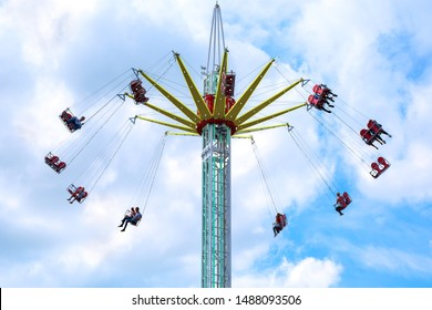 Zwolle, The Netherlands - 08 14 2019: Flying swing carousel in action against cloudy sky. People enjoy a ride on a flying swing ride at an amusement park.