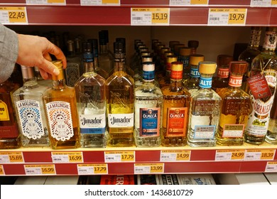 ZWOLLE, THE NETHERLANDS - FEBRUARI 21, 2019: Various Tequila brands in a store. A Hand selecting a bottle of Tequila at a Sligro wholesale