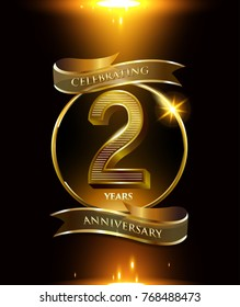 2 years anniversary logo with shiny ribbon and golden ring isolated on black background