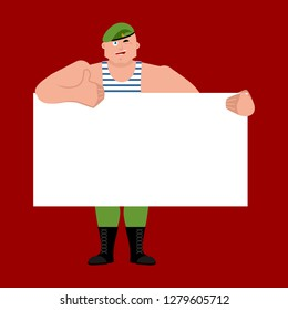 23 February. Defender of Fatherland Day.  Russian soldier holding banner blank. Airborne troopsand white blank. Paratrooper Military in Russia  thumb up and winks joyful emotion.