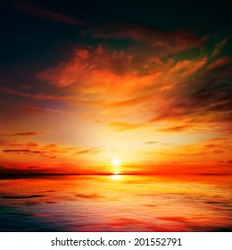abstract dark nature background with sea red sunset and clouds