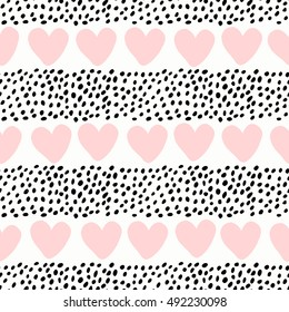 Abstract seamless pattern with hearts and dots in pastel pink and black on white background.