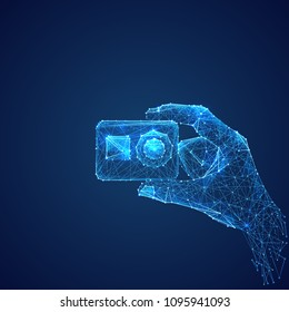 Abstract vector image of action camera in hand . Low poly wire frame illustration. Lines and dots. RGB Color mode. Video blog concept. Polygonal art.