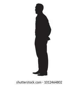 Adult man standing with his hands behind his back. Side view, vector isolated silhouette