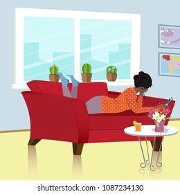 The African American girl lying relaxed on the couch and listening to music on the mobile phone