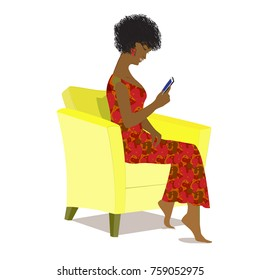 African American  girl sitting in a yellow armchair and using a mobile phone