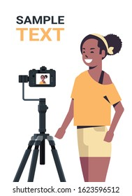 african american woman blogger recording video blog with digital camera on tripod live streaming social media blogging concept portrait vertical copy space vector illustration