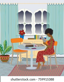 African American woman sitting by the table and reading book, with stack of books next to her