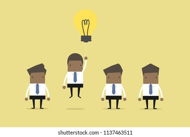 African businessman flying out by light bulb of idea.
