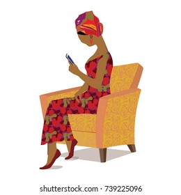 African girl sitting in a retro armchair and using a mobile phone