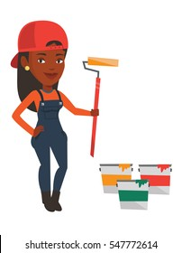 African-american painter in uniform holding paint roller in hands. Young house painter at work. Smiling painter standing near paint cans. Vector flat design illustration isolated on white background.
