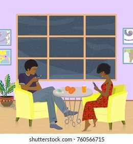 The African-American young couple is sitting in the living room and everyone looks into their cell phone