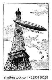 Airship is rounding the Eiffel Tower navigate through the air under its own power lift from large gas bags vintage line drawing or engraving illustration.