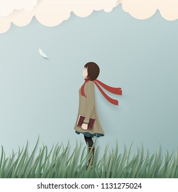 Alone girl in winter coat on green grass with book.Paper art concept background.