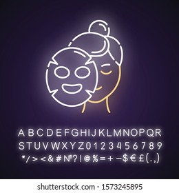 Applying sheet mask neon light icon. Skin care procedure. Hydrogen mask. Face cotton product. Cosmetics, makeup. Glowing sign with alphabet, numbers and symbols. Vector isolated illustration