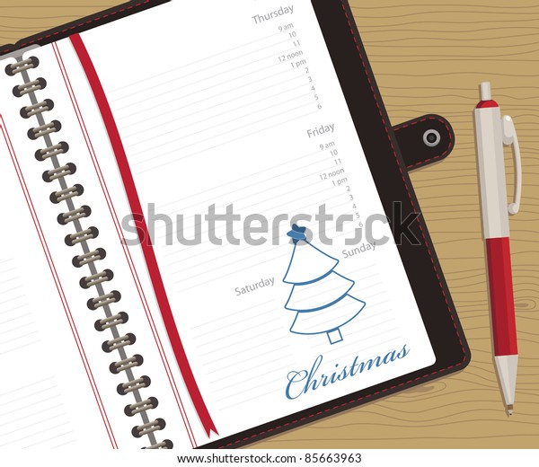 appointment book showing christmas day, with clipping mask and pen on wood background