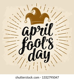 April fool's day calligraphic handwriting lettering with jester cap engraving. Vector color illustration isolated on a beige background. For web, poster