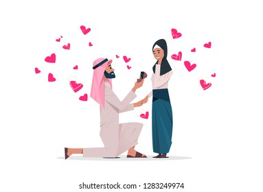 arab man kneeling holding engagement ring proposing arabic woman marry him happy valentines day concept couple in love marriage offer over heart shapes horizontal