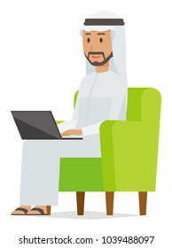 An arab man wearing ethnic costumes is sitting on a sofa and operating a laptop computer