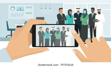 Arab muslim business people posing together and meeting in a corporate office building, a man is taking a picture using a smartphone