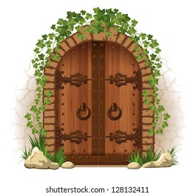 Arched medieval wooden door in a stone wall, with ivy