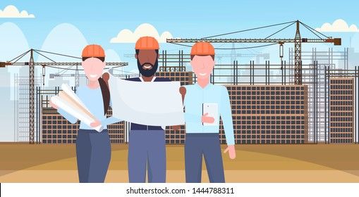 architects working with blueprints mix race engineers team discussing new building project during meeting builders in helmet teamwork concept construction site background portrait horizontal