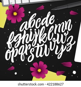 Artwork with ABC set. Black desk with vector characters, post-it note, pen and pink flowers. Typography Background. Cursive Modern Lettering Alphabet. Perfect font for your projects.