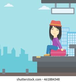 An asian young woman sitting on a suitcase at the train station on the background of arriving train. Woman waiting for a train at the platform. Vector flat design illustration. Square layout.