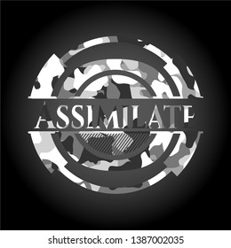 Assimilate written on a grey camouflage texture