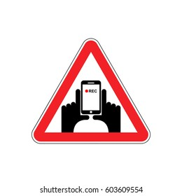 Attention Vertical video. Hand and smartphone to record. Road sign on red triangle. symbol Caution