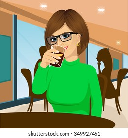 attractive brunette young woman with glasses drinking beverage and sitting at table in cafe