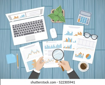 Auditing concepts. Businessman auditor inspects assessing financial documents. Man's hands with magnifying glass above graphics and charts. Research,management, planning, accounting, analysis, data.