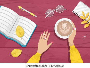 Autumn flat lay background with workplace in a cafe. Women's hands holding a Cup of cappuccino. Burgundy wooden background with yellow autumn leaves. Book, notebook, eye glasses.