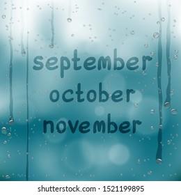 Autumn months written on wet glass. Rainy window and hand written september october november text dark blue sky background