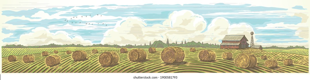 Autumn rural landscape in panoramic format with a farm and bales of hay in the foreground