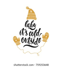 Baby it's cold outside. Hand drawn calligraphy text. Holiday typography design with hat and mittens. Black and gold christmas greeting card. Vector illustration EPS10.