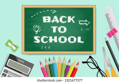 Back to school text on chalkboard with school supplies on green background