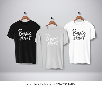 Basic Black, gray and white short sleeve T-Shirts Mock-up clothes set hanging isolated on wall. Front side view with lettering for your design or logo.